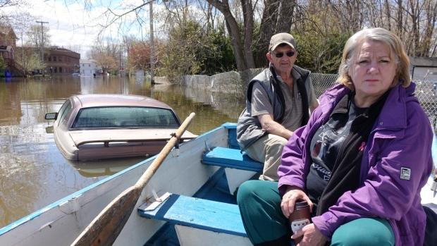 زوجان يغادران في قارب منزلهما الذي غمرته المياه في غاتينو با/ Ashley Burke/CBC/ هيئة الاذاعة الكنديّة