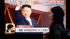تقرير متلفز يظهر فيه زعيم كوريا الشماليّة كيم جونغ اون على شاشة مرفوعة في الشارع/Toru Hanai/Reuters