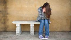 شابّة وضعت رأسها بين يديها وبدت عليها علامات القلق/Paulius Brazauskas/Shutterstock