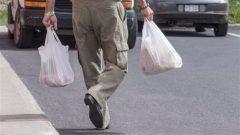 شخص يحمل حاجيّاته في اكياس من البلاستيك PC/ Paul Chiasson