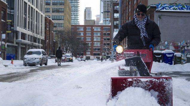 رجل يرفع الثلوج من أمام منزله في تورونتو في 02-03-2016//Christopher Katsarov/CP