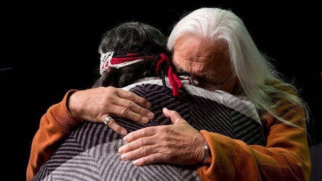اثنان من سكّان كندا الأصليّين يتعانقان خلال لقاء مع لجنة الحقيقة والمصالحة في فانكوفر/PC/DARRYL DYCK