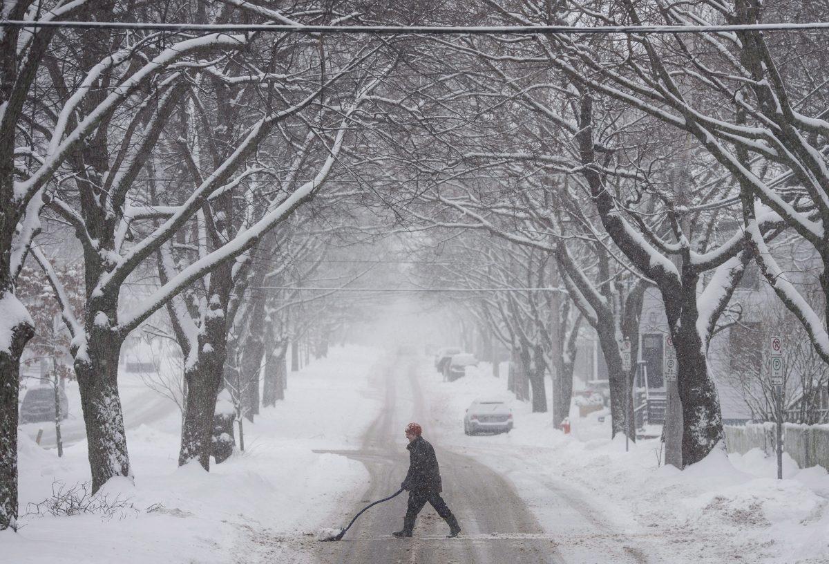 سيّدة تجرف الثلوج خلال عاصفة ثلجيّة ضربت هليفاكس في 17-01-2018//Darren Calabrese/CP