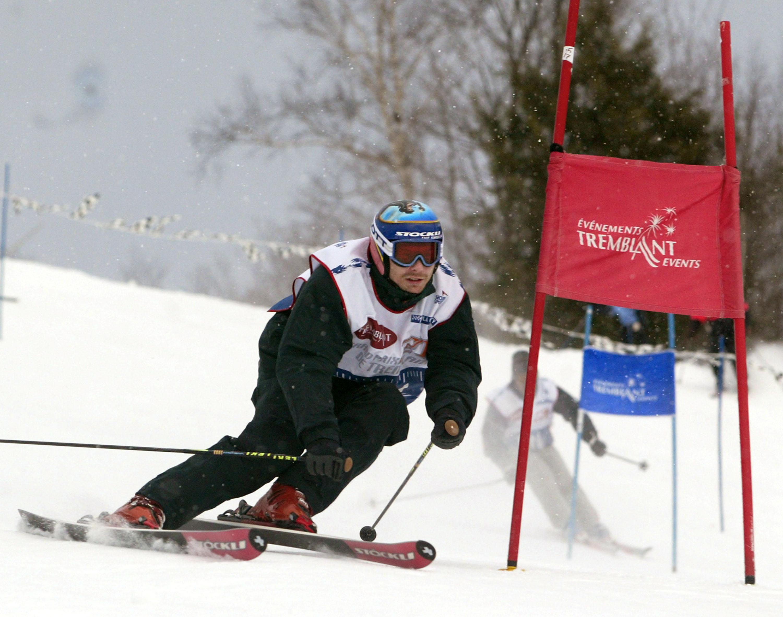 بطل سباق السيّارات الكندي جاك فيلنوف يتزلّج خلال حفل خيري في مون ترامبلان في كيبيك في 03-12-2003/REUTERS/Christinne Muschi CM