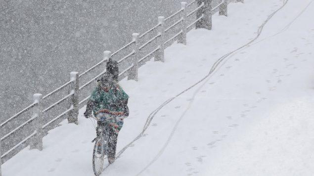 درّاج يتنقّل بدرّاجته وسط عاصفة ثلجيّة ربيعيّة في 06 نيسان ابريل 2016/REUTERS/Chris Wattie
