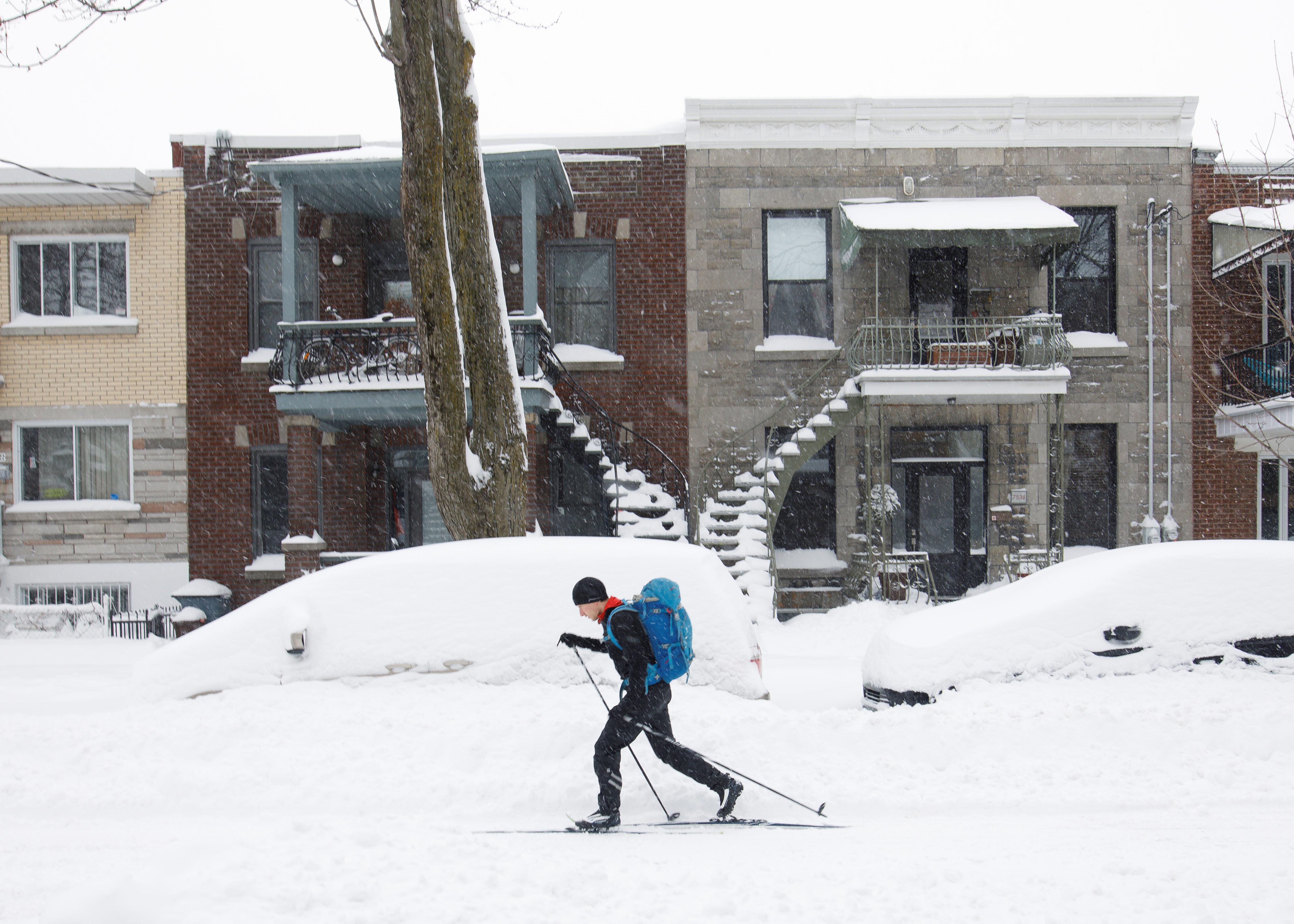 رجل يتزحلق على الثلج في أحد شوارع مونتريال وسط سيّارات غمرتها الثلوج بعد العاصفة التي ضربت العديد من أنحاء مقاطعة كيبيك في 15-03-2017/REUTERS/Dario Ayala