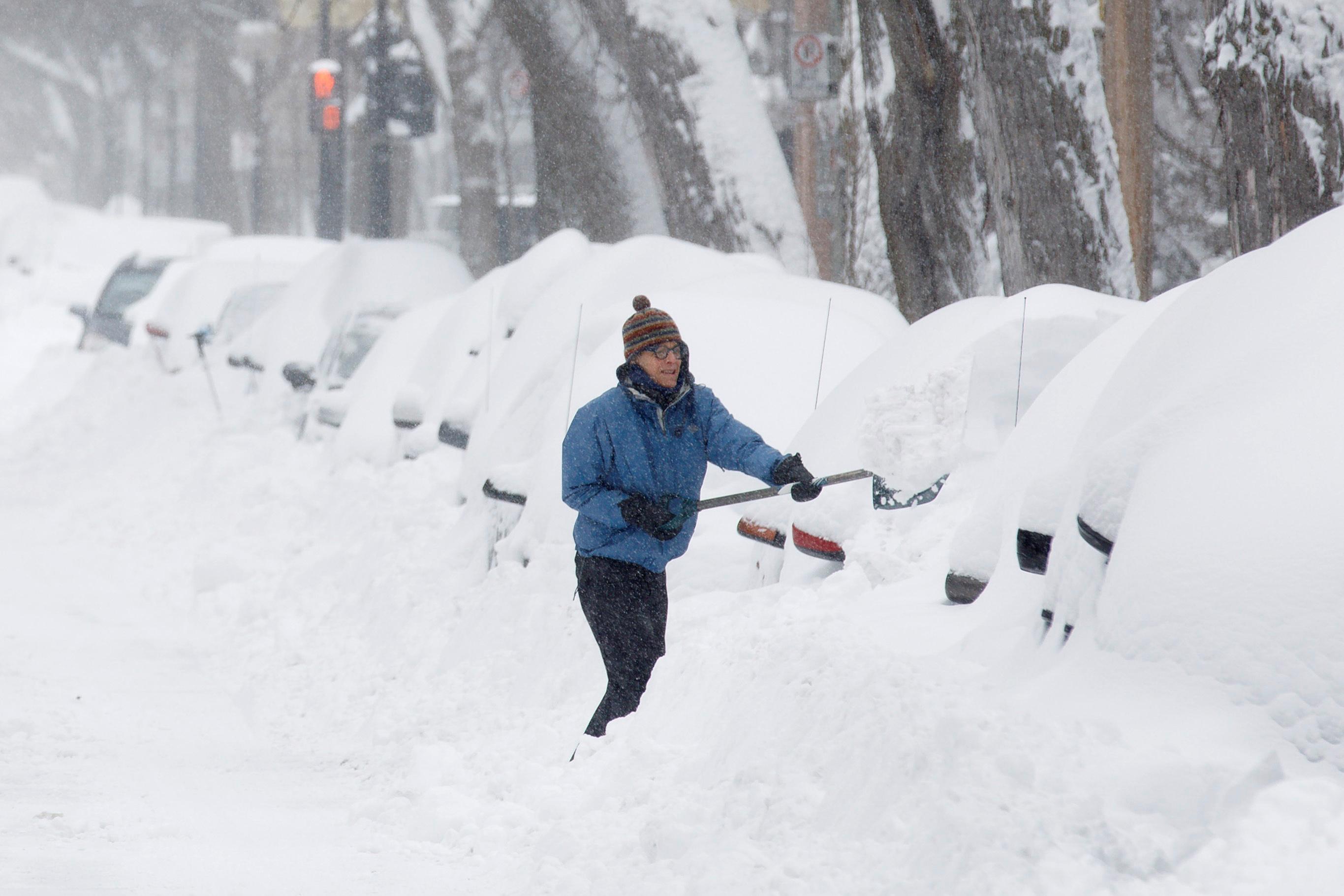 سيّدة ترفع الثلوج عن سيّارتها بعد عاصفة ثلجيّة ضربت مدينة كيبيك في 15-03-2017/REUTERS/Dario Ayala TPX IMAGES OF THE DAY