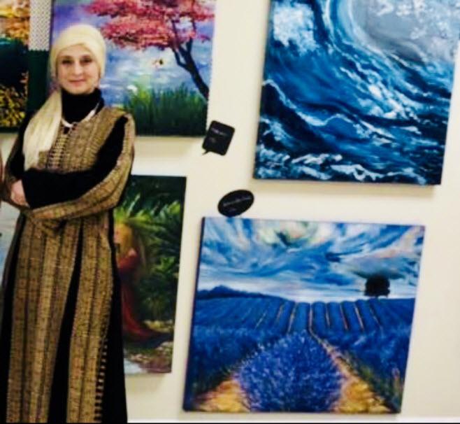 عُلا السرّاج أمام لوحاتها في آخر معرض شاركت فيه في مونتريال بدعوة منالمؤسسة الكندية-الفلسطينية/عُلا السرّاج