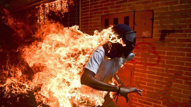 محتج فنزويلي تلتهمه النيران في وسط احتجاجات ضد الرئيس الفنزويلي نيكولا مادورو في كاراكاس في العام 2017 ، صورة فازت بجائزة الوورد بريس للعام 2018 حقوق الصورة: AFP