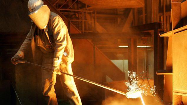 عامل فولاذ في ألمانيا يحرك المعدن أثناء انصهاره مع الإشارة إن هذه الصناعة قد تتحمل انعكاسات سلبية وفق قرار الرئيس الأميركي برفع التعرفات ىالجمركية/وكالة الصحافة الكندية