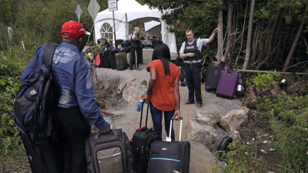 طالبو لجؤ يدخلون كندا بصورة غير شرعيّة الحدود الكنديّة الأميركيّة/Charles Krupa/AP