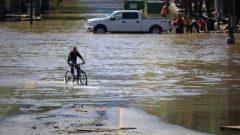 درّاج يتنقّل وسط شارع غمرته المياه وظهر فيه عدد من المارّة إلى جانب سيّارة بيك آب/CBC/Rafferty Baker/هيئة الاذاعة الكنديّة