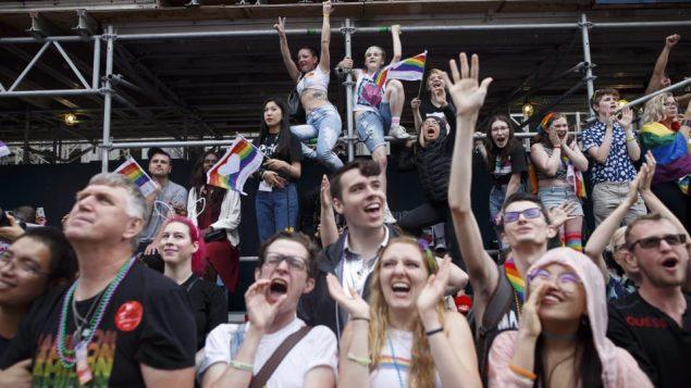 شبّان وشابّات يشاركون في مسيرة مثليّي الجنس في تورونتو/Cole Burston/CP