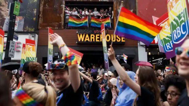 مشاركون يرفعون أالأعلام بألوان قوس القزح في مسيرة المثليّين في تورونتو في 24/06/2018/Cole Burston/CP