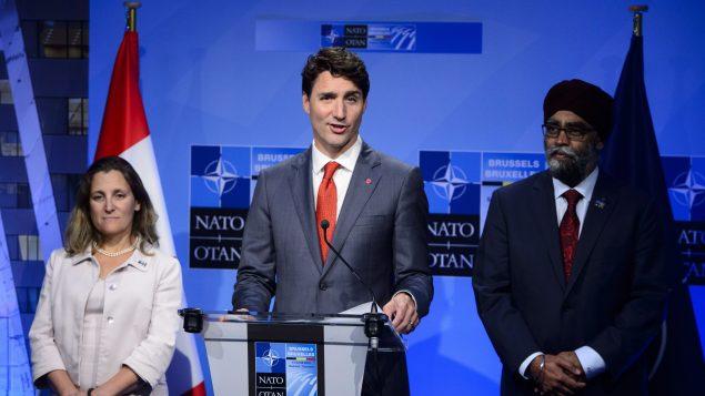رئيس الحكومة الكنديّة جوستان ترودو (في الوسط) ووزير الدفاع هارجيت سجان ووزيرة الخارجيّة كريستيا فريلاند خلال مؤتمر صحافي عقده ترودو في نهاية قمّة حلف شمال الأطلسي في بروكسيل في 12-07-2018/Sean Kilpatrick/CP