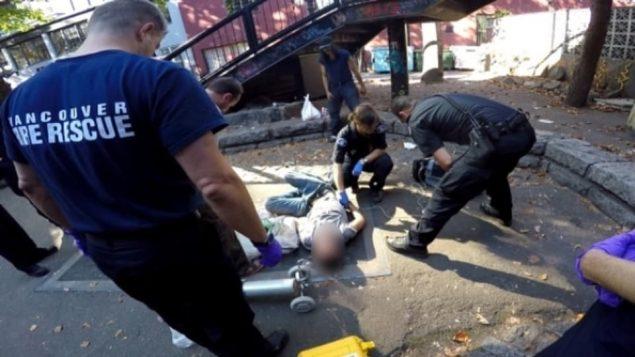مسعفن يساعدون أحد المدمنين المرتمي على الأرض/Radio-Canada