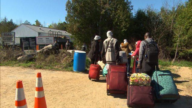 مجموعة من طالبي اللجوء على الحدود الأميركية مع كيبيك ويبدو عناصر الشرطة الكنديون بانتظارهم/راديو كندا