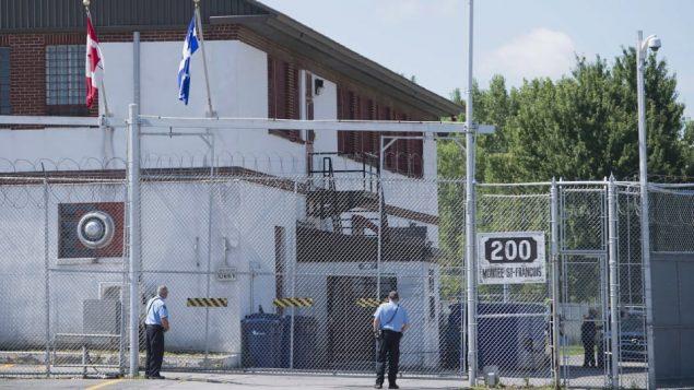 حارس أمام مركز احتجاز المهاجرين في مدينة لافال/Graham Hughes/CP