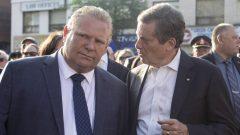 إلى اليمين عمدة تورنتو جون توري يتحدث إلى رئيس حكومة أونتاريو دوغ فورد/الصحافية الكندية