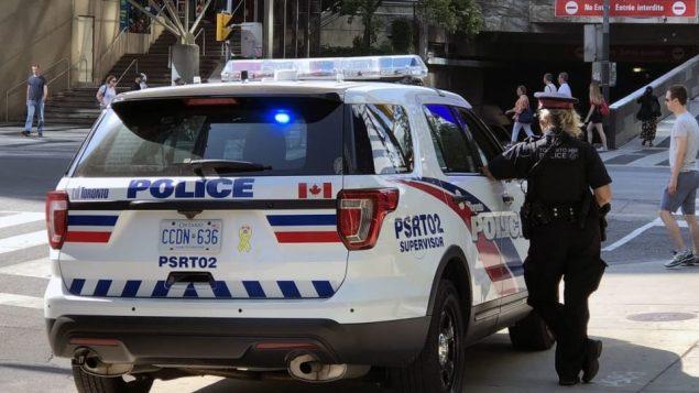شرطيّة تقف بجانب سيّارة تابعة لشرطة تورونتو/CBC/Ian Kalushner/هيئة الاذاعة الكنديّة