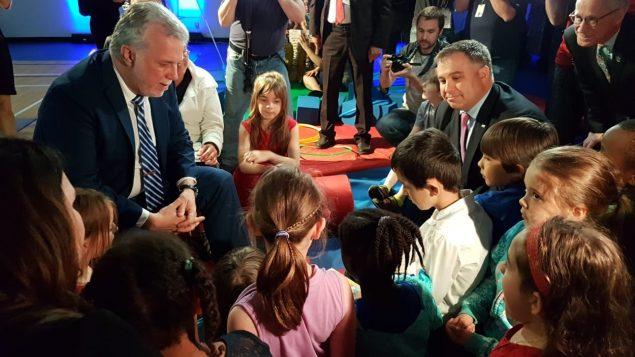رئيس حكومة كيبيك فيليب كويار برفقة وزير التعليم سبستيان برو مع أطفال هم جيل المستقبل التعليمي في كيبيك/راديو كندا