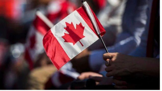 يد ترفع العلم الكندي/(Mark Blinch/CP