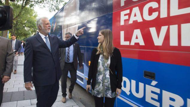 رئيس حكومة كيبيك الخارج فيليب كويار أمام الباص الانتخابي/Jacques Boissinot/CP
