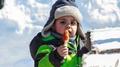 طفل بثياب الثلج يأكل الحلوى تحت سماء زرقاء /ميشال اسكندر