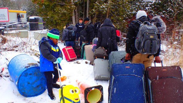 مجموعة من المهاجرين النايجيريين غير النظاميين تدخل كندا عبر طريق روكسهام في لاكول في كيبيك آتية من الولايات المتحدة - René Saint-Louis/Radio Canada