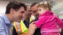 رئيس الحكومة الكندية جوستان ترودو يسقبل أحد أفواج اللاجئين السوريين (أرشيف) -Nathan Denette/Canadian Press