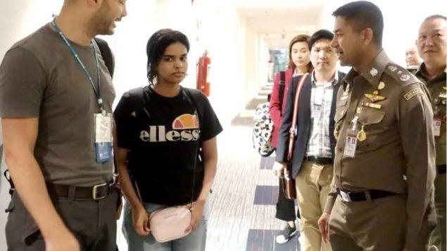 رهف محمّد القنون في فندق في محيط مطار بانكوك وسط رئيس شرطة الهجرة التايلاندي (إلى اليمين) ومسؤول من الأمم المتّحدة/Thai Immigration Bureau/EFE/EPA