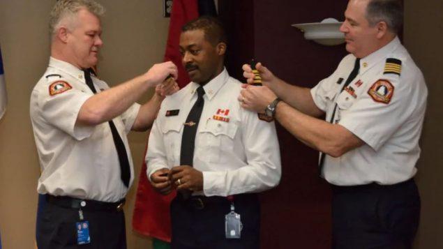 كوري بيلز يتسلّم أشرطته كرئيس مساعد في جهاز الإطفاء في مدينة هاليفاكس من رئيس الجهاز كين ستوبينغ (إلى اليسار) ونائب الرئيس بيتر اندروز/Sean Dewitt