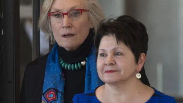 وزيرة العلاقات مع السكّان الأصليّين كارولين بينيت (إلى اليسار) و كلوديت كوماندا التي تشارك في الدعوى الجماعيّة ضدّ الحكومة/Adrian Wyld/CP