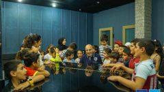 """الموسيقي اللبناني جاد رحباني مع مجموعة من الأطفال يشاركون في ورشة عمل موسيقيّة في غطار مشروع """"البوم 11"""" الذي اطلقته منظّمة اليونيسيف/موقع اليونيسيف"""