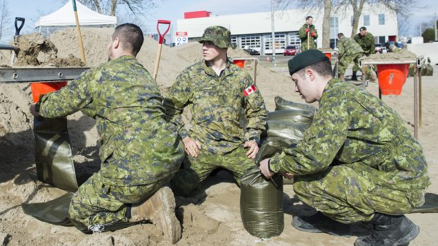 جنود كنديّون يساعدون في ملء أكياس الرمل في مدينة ريغة غرب مقاطعة كيبيك في 21/04/2019//Graham Hughes/CP
