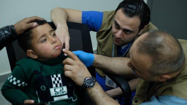 الدكتور سامي مبيّض 0في الوسط) يعاين طفلا سوريّا في لبنان في إطار مشاركته في مهمّة طبيّة انسانيّة لمساعدة اللاجئين السوريّين/سامي مبيّض/SAMS/tdsf/فيسبوك