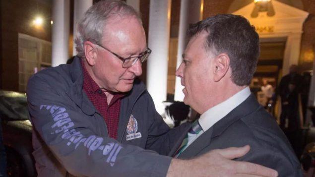 زعيم اللببراليّين ورئيس الحكومة الخارج ويد ماكلاكلين (إلى اليسار) يهنّئ زعيم المحافظين دنيس كينغ الذي فاز بحكومة أقليّة/Andrew Vaughan/CP