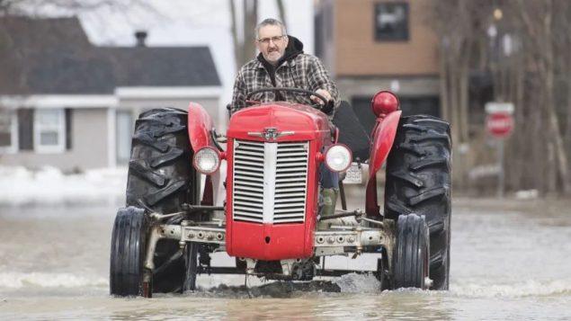 رجل يقود جرّارا زراعيّا في مدينة ريغو الواقعة في غرب مقاطعة كيبيك/Graham Hughes/CP