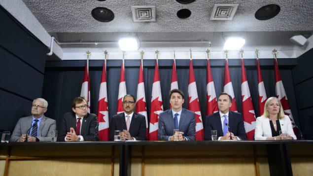 رئيس الحكومة جوستان ترودو (الثالث من اليمين) محاطا بعدد من الوزراء يتحدّث عن موافقته على مشروع توسيع أنبوب ترانس ماونتن في 18-06-2019/Sean Kilpatrick/CP