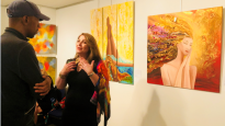 زينب شعبان تتحدث عن معاني ورموز لوحاتها لأحد زوار المعرض يوم السبت الماضي/بعدسة كوليت ضرغام