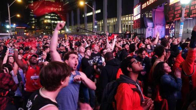 """أنصار فريق الرابتورز يتابعون إحدى المباريات على شاشات كبيرة في ما يسمّى """"حديقة جوراسيك"""" خارج ملعب سكوتيابنك للهوكي في تورونتو - Radio Canada / Rozenn Nicolle"""