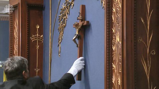 أحد موظفي الجمعية الوطنية في كيبيك وهو ينزع الصليب من القاعة الزرقاء حيث يجتمع النواب - Radio Canada