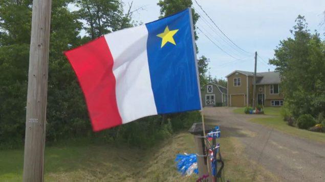 العلم الأكادي هو العلم الفرنسي مع نجمة صفراء إلى أعلى اليمين/Julien Lecacheur/Radio-Canada