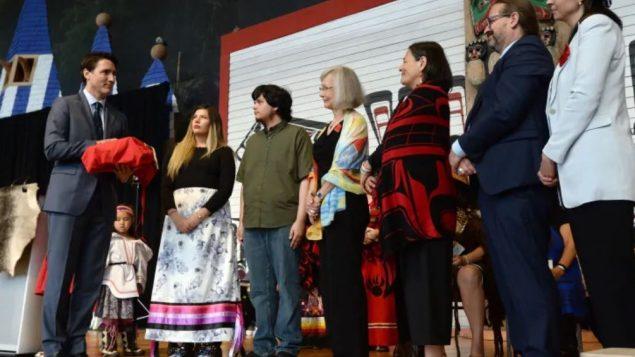 رئيس الحكومة جوستان ترودو (إلى أقصى اليسار) يتسلّم تقرير لجنة التحقيق في مقتل واختفاء نساء من السكّان الأصليّين/(Adrian Wyld/CP