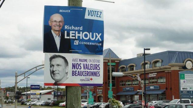 زعيم حزب الشعب في كندا ماكسيم برنييه المرشّح عن منطقة بوس في إعلان انتخابي ( في أسفل الصورة) وظهر في أعلى الصورة منافسه مرشّح حزب المحافظين ريشار لوهو/Marc-Antoine Lavoie/ Radio-Canada