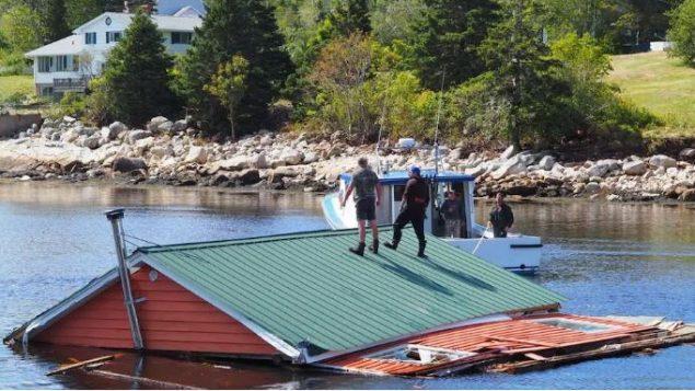 قارب يقطر منزلا غمرته المياه في هيرينغس كوف في مقاطعة نوفا سكوشا/Elisa Serret/Radio-Canada