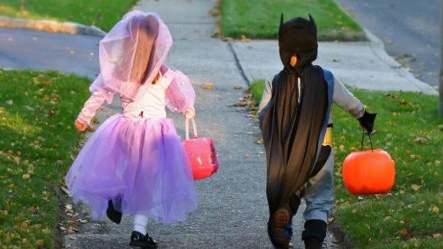أطفال متنكّرون بمناسبة عيد الهالووين يجمعون الحلوى - Shutterstock