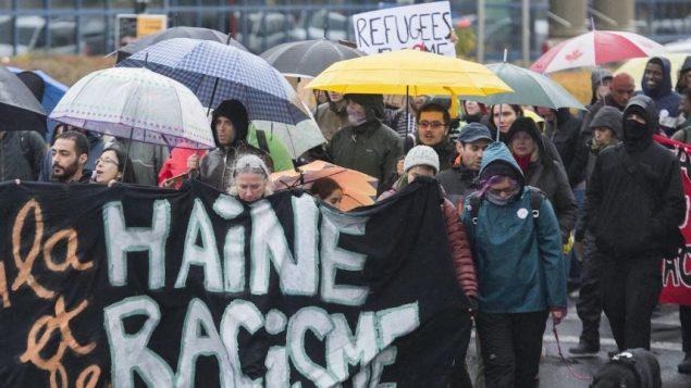 أبرز المشاركون في المظاهرة ما يصفونه بالجوانب التمييزية للقانون الذي يحظر ارتداء الرموز الدينة على موظفي الدولة في موقع سلطة بما فيهم المعلّمات اللائي يرتدين الحجاب الإسلامي - The Canadian Press / Graham Hughes