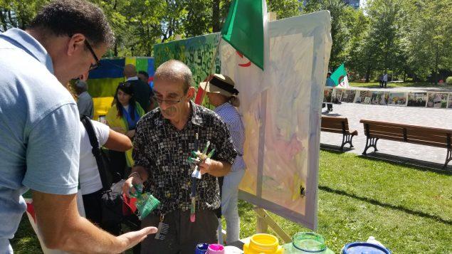 الفنان التشكيلي، علي كيشو  مع أحد المشاركين في رسم لوحة العلم الجزائري- Photo : samir Bendjafer
