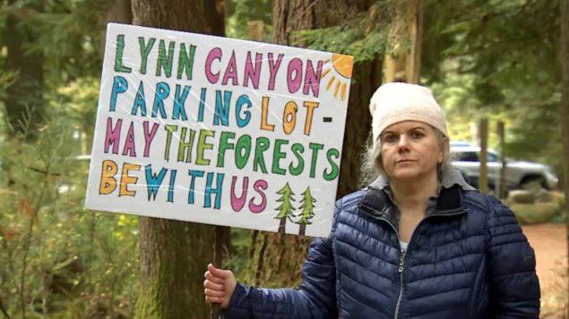 المواطنة كيم هيوز ترفع لافتة تعبّر فيها عن معارضتها لقطع أشجار في محيط متنزّه لين كانيون في شمال فانكوفر/Jon Hernandez/CBC/راديو كندا